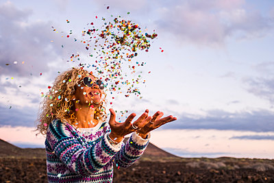 Happy blond woman throwing confetti in the air, Tenerife, Spain - p300m2156685 by Simona Pilolla
