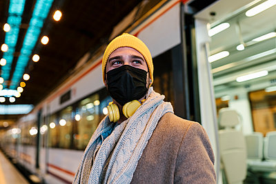 Man wearing face mask looking away while standing against train at station - p300m2251074 by Ezequiel Giménez