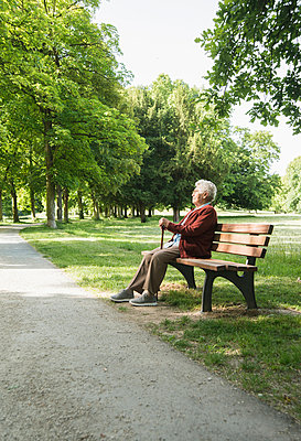 Senior woman sitting on park bench in park - p429m942740f by Uwe Umstaetter