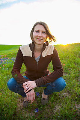 Portrait of a young woman in a meadow with wildflowers at sunset; Waco, Texas, United States of America - p442m2074033 by Blake Kent