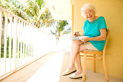 Older Caucasian solving crossword puzzle on balcony - p555m1408811 by Shestock