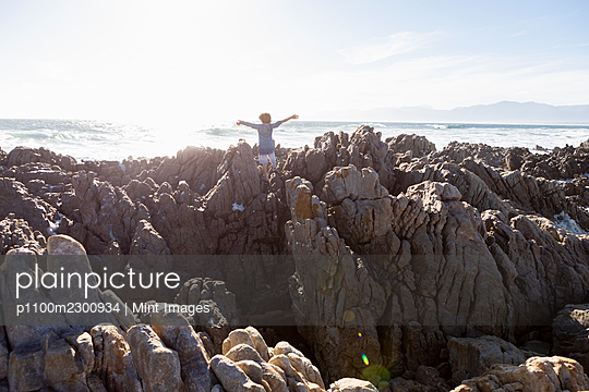 Boy exploring the jagged rocks and rock pools on the Atlantic Ocean coastline  - p1100m2300934 by Mint Images