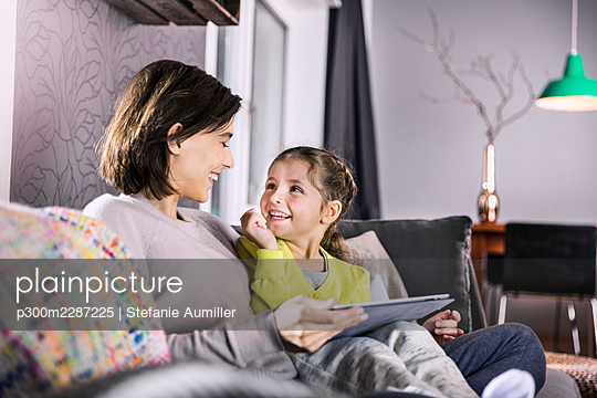 Smiling mother with digital tablet looking at daughter while sitting on sofa - p300m2287225 by Stefanie Aumiller