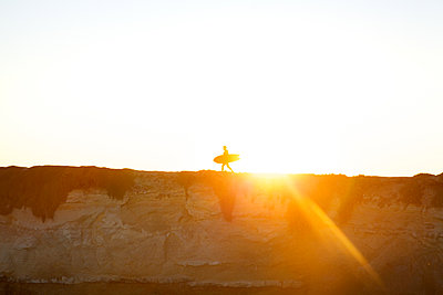 Silhouette of surfer against the light - p1106m1589465 by Angela DeCenzo