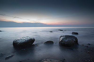 Large stones on a pebble beach at the Baltic Sea in the evening mood, Wustrow, Darss, Mecklenburg Vorpommern, Germany - p1316m1202888 by Christoph Olesinski