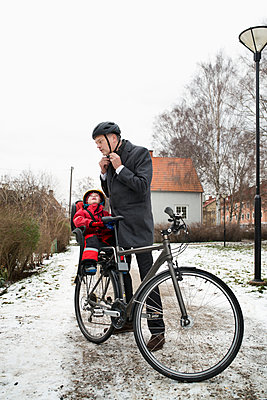 Sweden, Sodermanland, Stockholm, Man wearing helmet standing by bicycle with son (2-3) on back seat - p352m1186933 by Julia Sjöberg