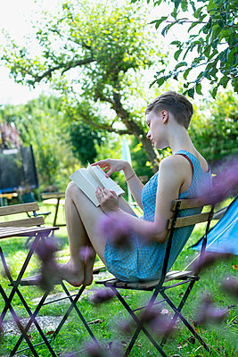 Young woman reading a book in the garden - p427m2134502 by Ralf Mohr