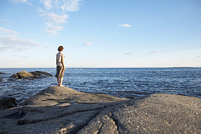 Woman standing on a rock - p4641266 by Elektrons 08