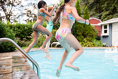 Girls jumping into swimming pool - p555m1303497 by JGI/Jamie Grill