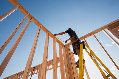Caucasian man measuring frame on construction site - p555m1478656 by Mike Kemp