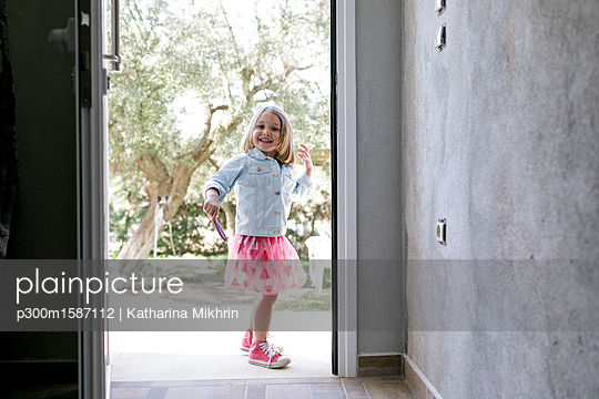 Portrait of laughing little girl standing in front of open entry door - p300m1587112 von Katharina Mikhrin