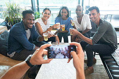 POV man with smart phone photographing friends drinking beers - p1023m2262106 by Himalayan Pics