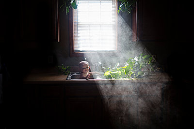 Portrait of shirtless baby girl playing in kitchen sink at home - p1166m1474067 by Cavan Images