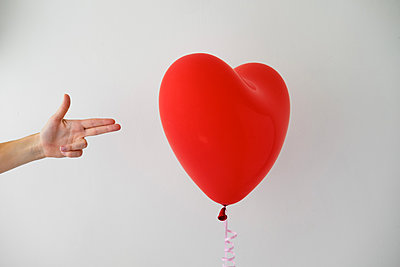 The hand in the form of a gun is aimed at a balloon in the shape of a heart - p1363m2031422 by Valery Skurydin