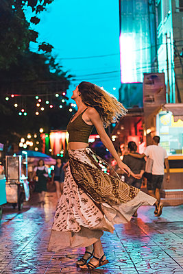 Thailand, Bangkok, young woman in the city dancing on the street at night - p300m1581428 by VITTA GALLERY