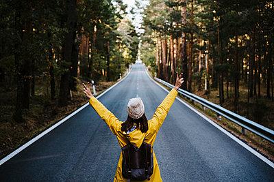 Woman in yellow raincoat standing on empty treelined road - p300m2242627 by Eva Blanco