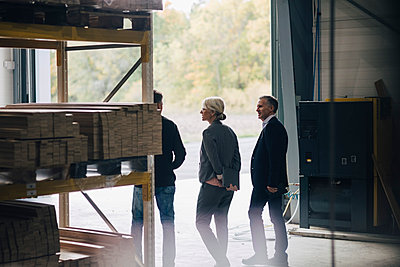 Business colleagues discussing while standing by rack at lumber industry - p426m1537011 by Maskot