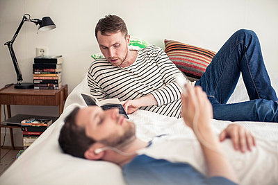 Young gay man reading book with partner listening music on bed at home - p426m811595f by Maskot