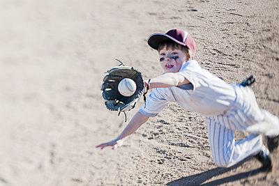 Caucasian boy catching baseball on field - p555m1305968 by Dennis Lane