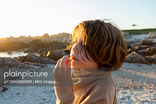 A boy on the beach at sunset, having a snack. - p1100m2300955 by Mint Images