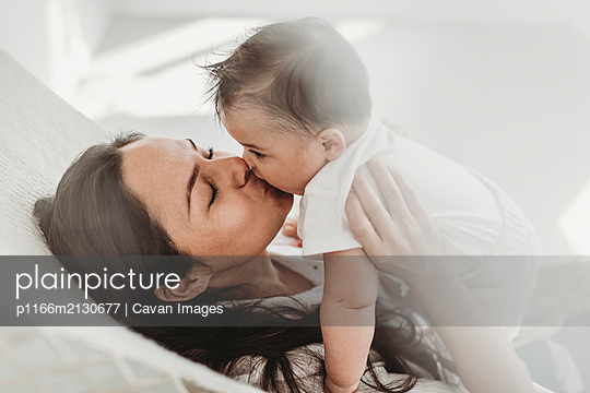 Mother kissing baby daughter hammock in natural light studio - p1166m2130677 by Cavan Images