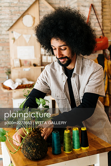 Afro man preparing kokedama houseplant on table at home - p300m2273563 by VITTA GALLERY