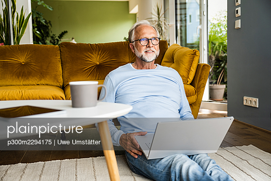 Mature man with laptop sitting on floor at home - p300m2294175 by Uwe Umstätter
