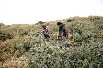 Mann hilft Frau den Hügel hoch zu klettern - p1212m1185632 von harry + lidy