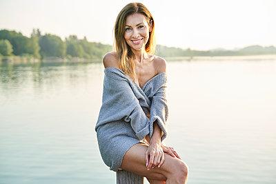 Portrait of mature woman sitting on pole at a lake - p300m2140672 by Philipp Nemenz