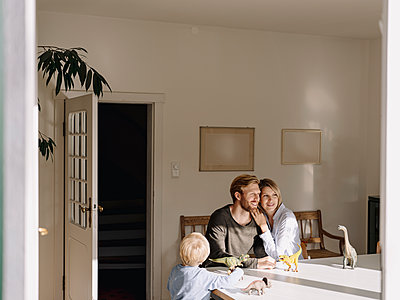 Relaxed family sitting at table at home with dinosaur figures - p300m2205528 by Kniel Synnatzschke