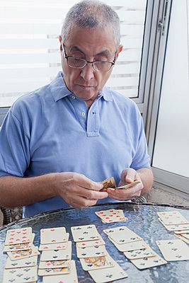 Hispanic man playing card game - p555m1301694 by REB Images