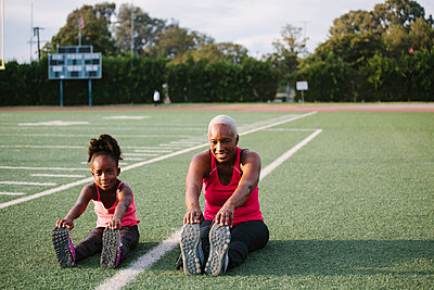 Grandmother and granddaughter stretching on football field - p555m1304767 by Shestock