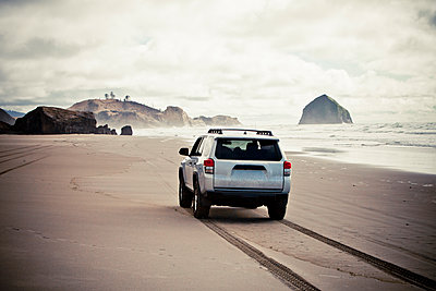 A SUV drives along a sandy beach. - p1424m1501438 by Christopher Kimmel