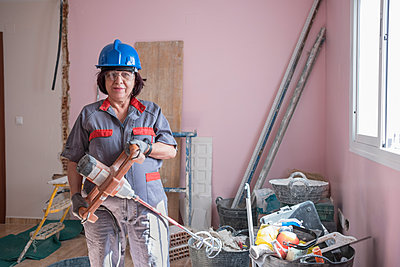 Senior woman with paint mixer at construction site - p300m1469730 by Jaen Stock