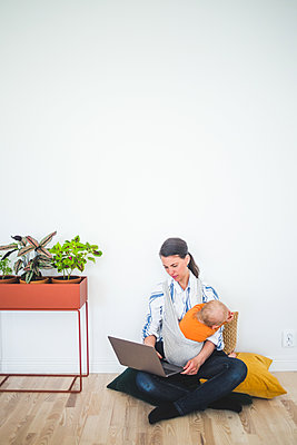 Full length of working mother using laptop while sitting with daughter against wall at home office - p426m2116984 by Maskot