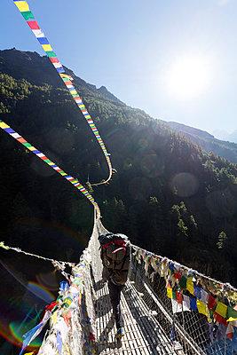 Porter crossing a suspension bridge decorated in Tibetan prayer flags, Sagarmatha National Park, UNESCO World Heritage Site, Khumbu Valley, Nepal, Asia - p871m1584075 by Christian Kober