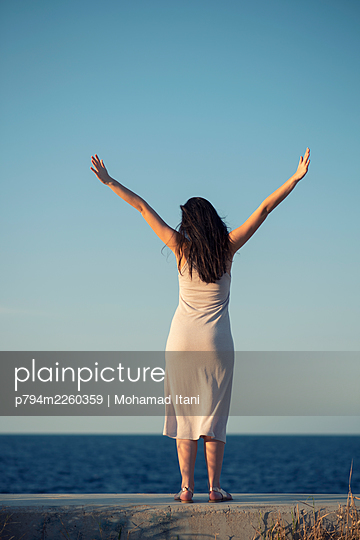 Happy young woman arms outstretched on the beach  - p794m2260359 by Mohamad Itani