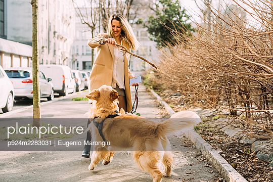 Italy, Young woman playing with dog on sidewalk - p924m2283031 by Eugenio Marongiu