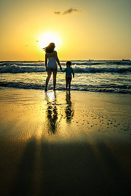 Mother and Child standing on beach at Sunset  - p1019m1467952 by Stephen Carroll