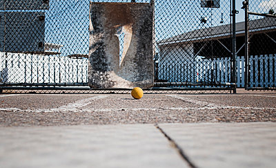 Ball against chainlink fence at playing field during sunny day - p1166m1509796 by Cavan Images