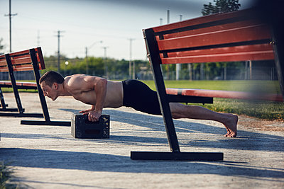 Young man doing push-ups - p312m1495366 by Johan Alp