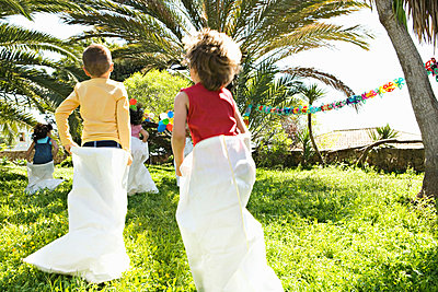 Children running sack race at birthday party - p6415113f by Maria Teijeiro