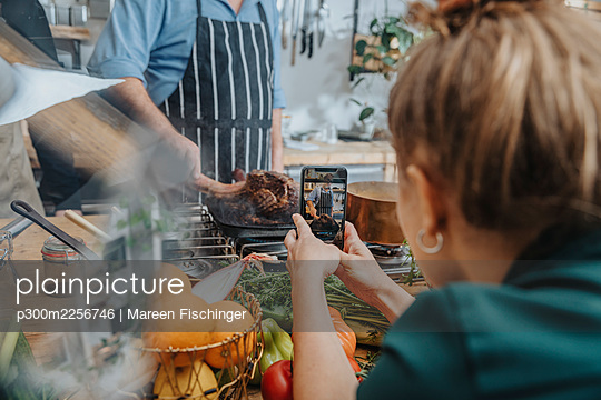 Young woman photographing chef cooking tomahawk steak in frying pan while standing in kitchen - p300m2256746 by Mareen Fischinger