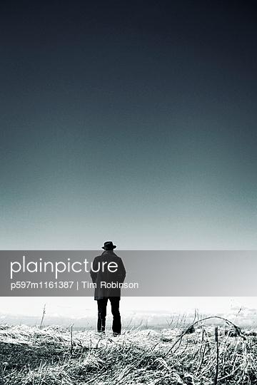 Mann mit Hut in Winterlandschaft - p597m1161387 von Tim Robinson