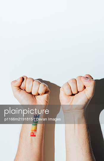 Gay guy's hand with a tattoo that says pride and nail polish. - p1166m2191815 by Cavan Images