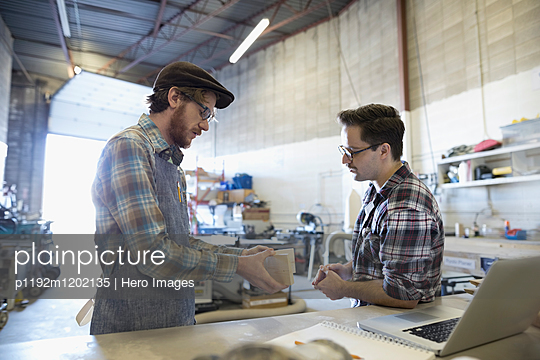 Male design professional engineers meeting at workbench in workshop - p1192m1202135 by Hero Images