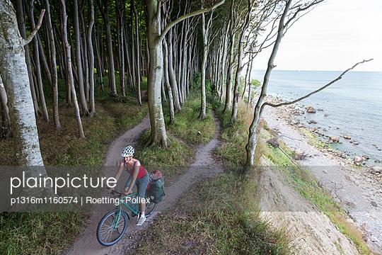 Radfahrerin fährt durch Gespensterwald, Höllenliet, Halbinsel Wittow, Insel Rügen, Mecklenburg-Vorpommern, Deutschland - p1316m1160574 von Roetting+Pollex