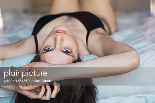 Young woman in underwear lying on bed - p300m1581319 von Kike Arnaiz