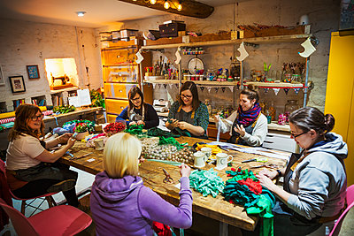 Group of people, women around a table in workshop, making paper flower wreaths. - p1100m1544332 by Mint Images