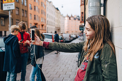 Girl taking selfie through smart phone with friends standing against wall - p426m1555967 by Maskot